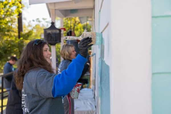 volunteer painting a house